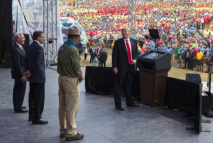 FILE - In this July 24, 2017, file photo, President Donald Trump turns and looks at, from left, Secretary of Health and Human Services Tom Price, Secretary of Energy Rick Perry, and Interior Secretary Ryan Zinke as he speaks at the 2017 National Scout Jamboree in Glen Jean, W.Va. For an administration that has spent 2017 throwing off headlines at a stunningly dizzying pace, the frenetic fortnight in the second half of July reached an unparalleled breakneck speed. (AP Photo/Carolyn Kaster, File)