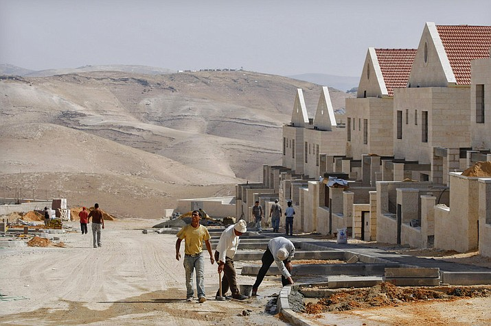 Palestinian men work at a construction site in the West Bank Jewish settlement of Maaleh Adumim, near Jerusalem. (AP Photo/Dan Balilty, File)