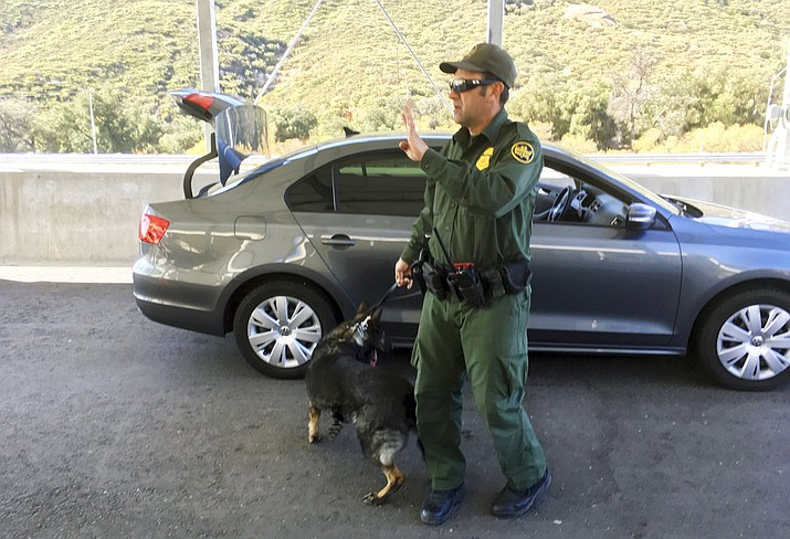 In this Thursday, Dec. 14, 2017 photo, a border patrol agent stops a vehicle at a checkpoint in Pine Valley, Calif. California legalizes marijuana for recreational use on Monday, Jan. 1, 2018, but that won't stop federal agents from seizing small amounts on busy freeways and backcountry highways. (AP Photo/Elliot Spagat)