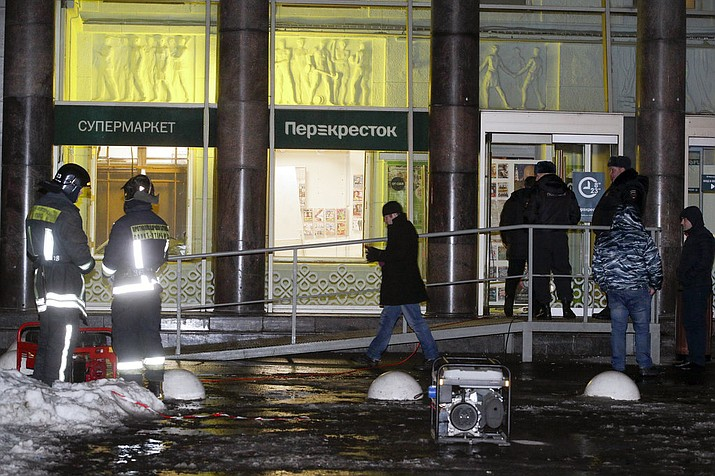 Police stand at the entrance of a supermarket, after an explosion in St.Petersburg, Russia, Wednesday, Dec. 27, 2017. Russian officials say at least 10 people have been injured by an explosion at a supermarket in St. Petersburg. (AP Photo/Dmitri Lovetsky)