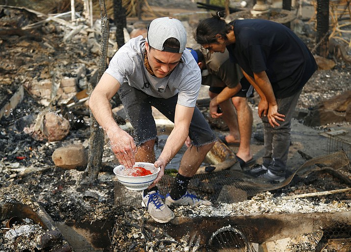 FILE - In this file photo, photo Logan Hertel fills a bowl of goldfish with water after he and some friends rescued them from a destroyed home on Parker Hill Court in Santa Rosa, Calif. Hertel is determined to reunite them with their owners. (Nhat V. Meyer/San Jose Mercury News via AP)