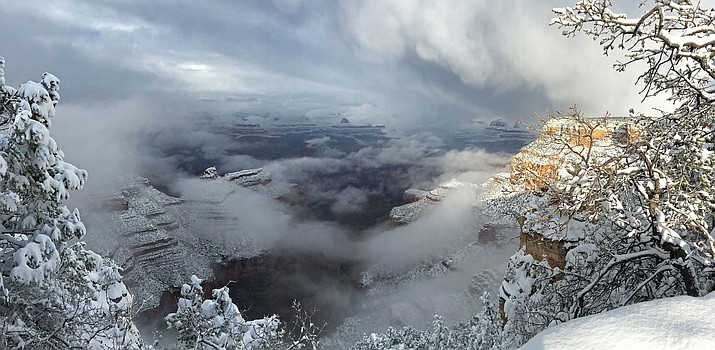 A winter storm is in progress with snow and clouds inside Grand Canyon and snow covering trees in this photo taken along the Canyon Rim Trail near Grandeur Point Jan. 7, 2016.
