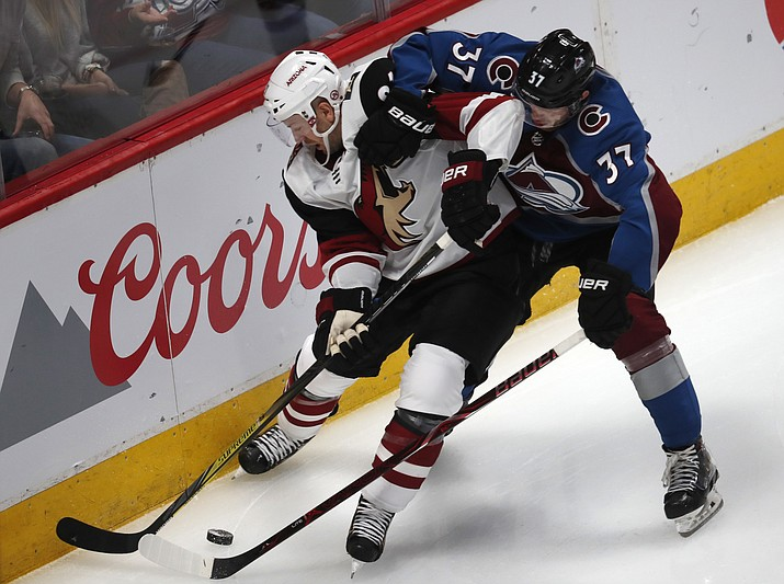 Arizona Coyotes defenseman Luke Schenn, left, vies for control of the puck with Colorado Avalanche left wing J.T. Compher during the third period of an NHL hockey game Wednesday, Dec. 27, 2017, in Denver. The Coyotes won 3-1. (David Zalubowski/AP)