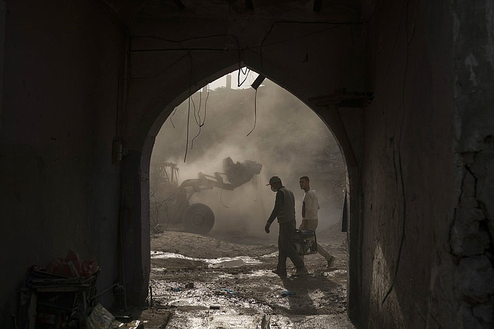 In this Nov. 18, 2017 photo, construction workers carry a generator as a bulldozer remove debris from destroyed shops in the Old City of Mosul, Iraq. Along the neighborhood's gutted roads, a handful of people are beginning to rebuild but the task ahead will take years _ and billions of dollars. (AP Photo/Felipe Dana)