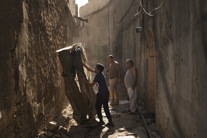 In this Nov. 16, 2017 photo, Mustafa Hansen, left, helps his father Ahmed Mohammed, center, and his grandfather Mohammed Tahar, clear the alley leading to their house in the Old City of Mosul, Iraq. Lacking enough funds from the government or international community, Iraqis have begun to rebuild on their own, dipping into savings and borrowing from friends and family. (AP Photo/Felipe Dana)