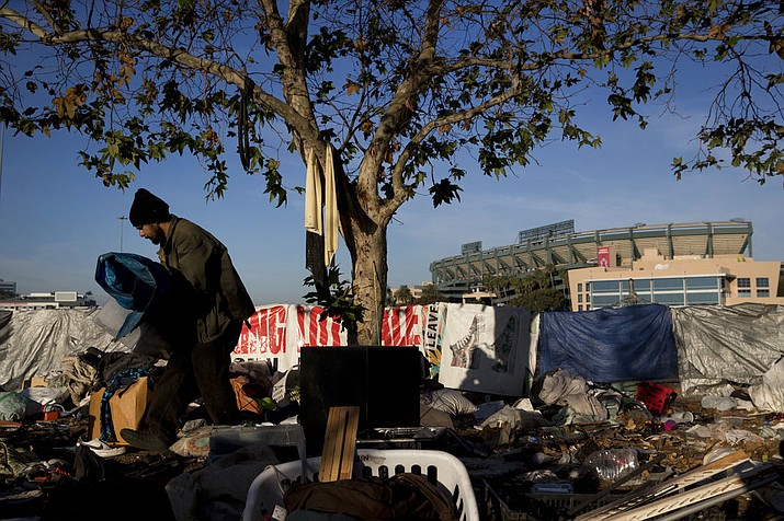 "Homeless Junior Sanchez, 29, carries a tarp he found in a pile of trash in a homeless encampment on the Santa Ana River trail near Angel Stadium Saturday, Dec. 2, 2017, in Anaheim, Calif. ""Toughest part being homeless is getting a plate of food and a shower,"" said Sanchez who said he became homeless after losing his job as cook. (AP Photo/Jae C. Hong)"