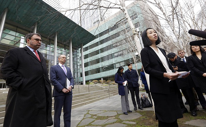 FILE- In this file photo, Mariko Hirose, right, a litigation director at the Urban Justice Center, addresses reporters as Mark Hetfield, president & CEO of HIAS, left, and Rabbi Will Berkowitz, Jewish Family Service of Seattle CEO, look on in front of a federal courthouse after speaking with media in Seattle.  (AP Photo/Elaine Thompson, File)