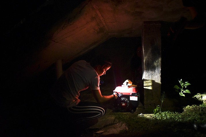 FILE - In this Dec. 21, 2017 file photo, barrio Patron resident Karina Santiago Gonzalez works on a small power plant in Morovis, Puerto Rico. Puerto Rico authorities said on Friday, Dec. 29, that nearly half of power customers in the U.S. territory still lack electricity more than three months after Hurricane Maria. (AP Photo/Carlos Giusti, File)