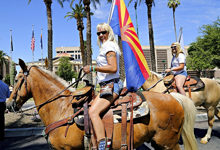 FILE--In this May 11, 2016, file photo, Shannon, left, and Raelee Lorance, right, advocates with the Salt River Wild Horses Management Group, ride horses in front of the Arizona Capitol before a press conference on a bill to protect the wild herd, in Phoenix, Ariz. The herd of wild horses living near Arizona's Salt River will get enhanced protection under a new agreement between state and federal agencies. (AP Photo/Ryan Van Velzer, file)