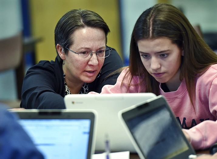Jennifer Rocca, left, a teacher librarian at Brookfield, Conn., High School, works with Ariana Mamudi, 14, a freshman in her Digital Student class. The required class teaches media literacy skills and has the students scrutinize sources for their on-line information. (AP Photo/Stephen Dunn)