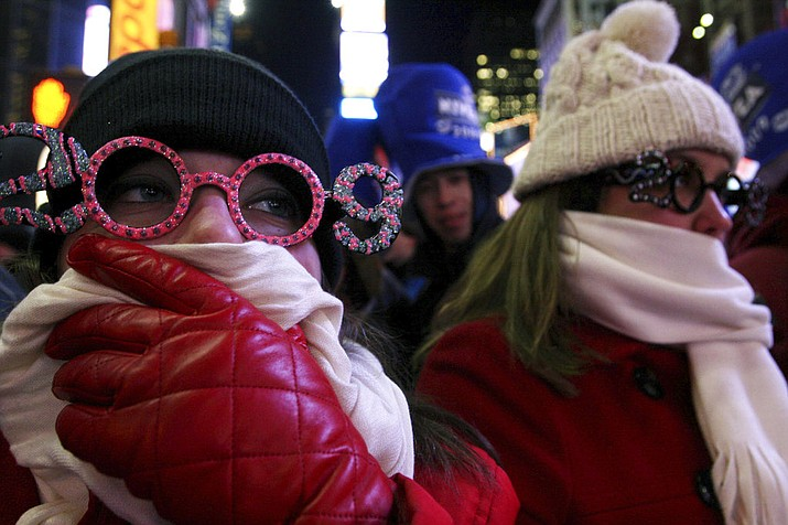 In this Dec. 31, 2008 file photo, Allison Smith of Jacksonville, Fla, left, tries to keep warm as she and others take part in the New Year's Eve festivities in New York's Times Square. Brutal weather has iced plans for scores of events in the Northeast U.S. from New Year's Eve through New Year's Day, but not in New York City, where people will start gathering in Times Square up to nine hours before the famous ball drop. (AP Photo/Tina Fineberg, File)