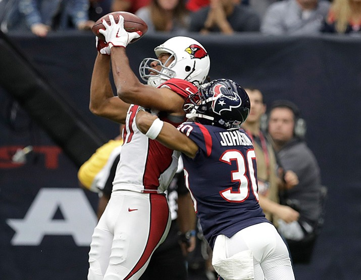 In this Nov. 19, 2017, file photo, Arizona Cardinals wide receiver Larry Fitzgerald (11) pulls in a catch for a touchdown over Houston Texans cornerback Kevin Johnson (30) during the first half of an NFL football game in Houston. Fitzgerald needs one catch on Sunday, Dec. 31, 2017, to have 211 straight games with a reception, tying Tony Gonzalez for the second-longest streak in league history. (David J. Phillip/AP, File)
