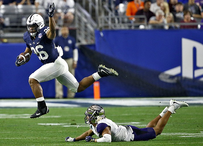 Penn State running back Saquon Barkley (26) leaps over Washington defensive back Myles Bryant (5) during the second half of the Fiesta Bowl NCAA college football game Saturday, Dec. 30, 2017, in Glendale.