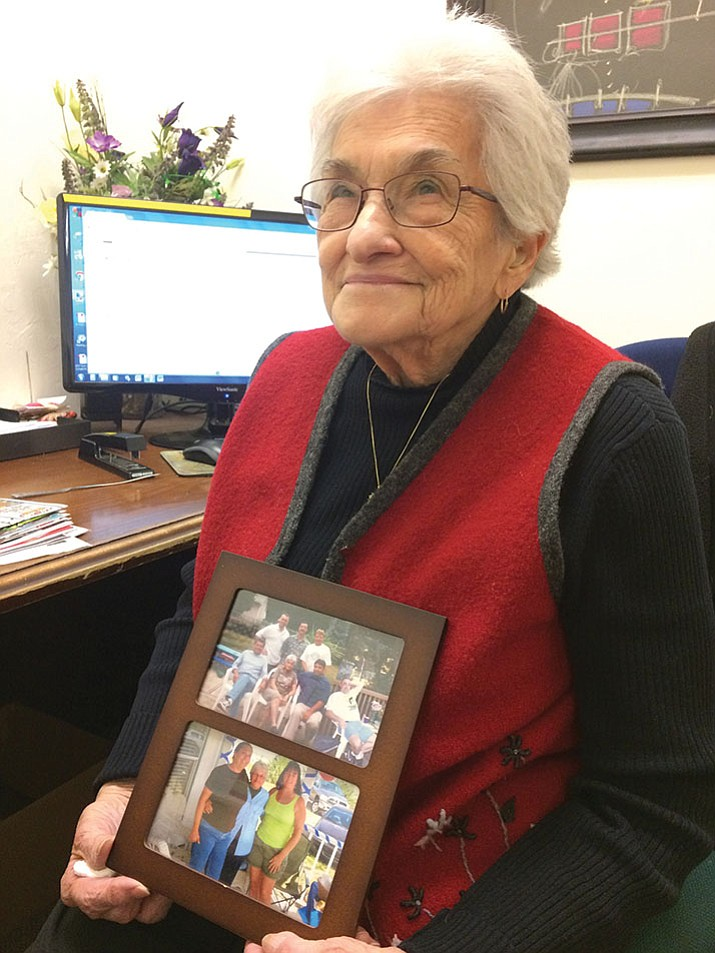 Her in her office, Jacquie Tobin holds a treasured photo of her family of eight children, 20 grandchildren and nine great-grandchildren. (Nanci Hutson/Courier)
