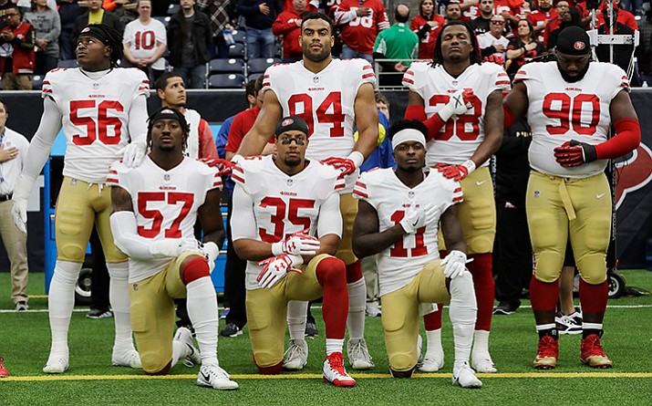 In this Dec. 10, 2017, file photo, San Francisco 49ers San Francisco 49ers' Eli Harold (57), Eric Reid (35) and Marquise Goodwin (11) kneel during the national anthem before an NFL football game against the Houston Texans, in Houston. (David J. Phillip/AP, File)