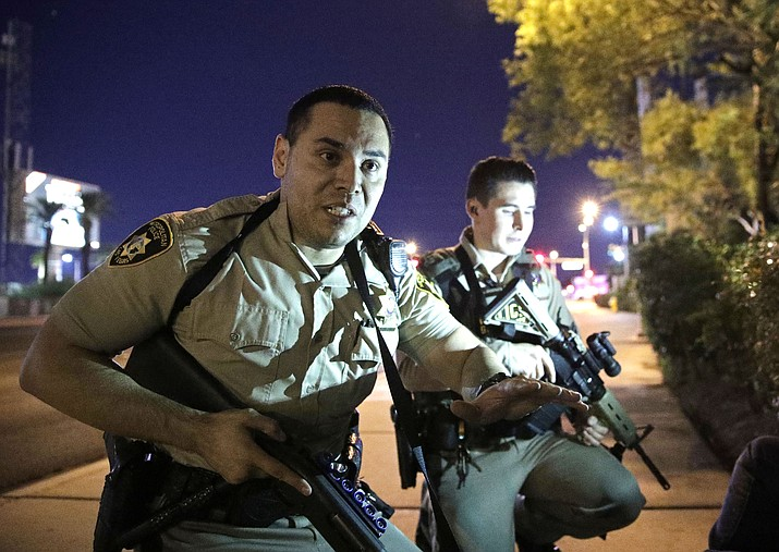 Police officers advise people to take cover near the scene of a shooting near the Mandalay Bay resort and casino on the Las Vegas Strip Oct 4 in Las Vegas.