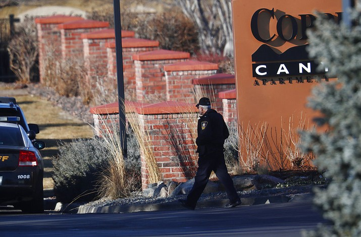 An investigator heads to the scene of shooting Sunday, Dec. 31, 2017, in Highlands Ranch, Colo. Authorities in Colorado say one deputy has died and multiple others were wounded, along with two civilians, in a shooting that followed a domestic disturbance in suburban Denver. (AP Photo/David Zalubowski)