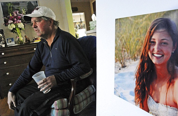 FILE - In this file photo, James Holleran, father of Madison Holleran, a University of Pennsylvania freshman who took her own life, talks about his daughter while sitting next to a favorite photo of her at his home in Allendale, N.J.  (April Saul/The Philadelphia Inquirer via AP, File)