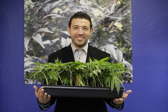 In this Dec. 29, 2017, photo, Khalil Moutawakkil, co-founder and CEO of KindPeoples, poses for a portrait with some marijuana plants in his dispensary in Santa Cruz, Calif. Californians may awake on New Year's Day to a stronger-than-normal whiff of marijuana as America's cannabis king lights up to celebrate the state's first legal retail pot sales. (AP Photo/Marcio Jose Sanchez)