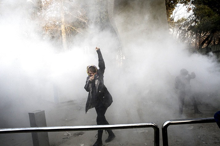 FILE - In this Saturday, Dec. 30, 2017 file photo taken by an individual not employed by the Associated Press and obtained by the AP outside Iran, a university student attends a protest inside Tehran University while a smoke grenade is thrown by anti-riot Iranian police, in Tehran, Iran.  (AP Photo, File)