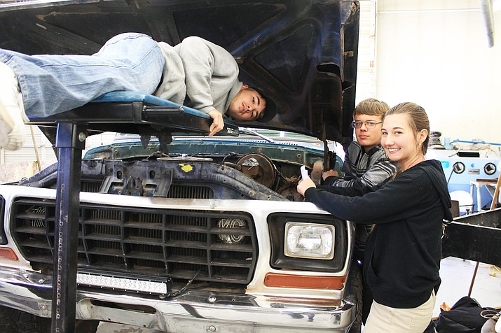 Sean Scott, Christina Richstad and Chris Gray work on Frankie Kramer's vintage Ford truck in the auto shop class.