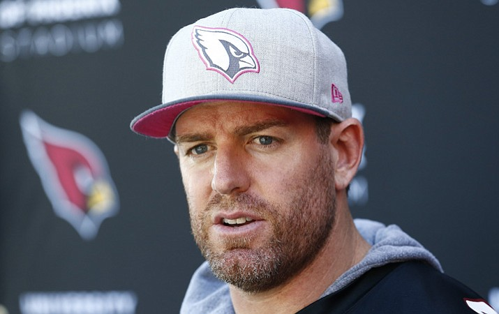 In this Wednesday, Oct. 11, 2017 file photo, Arizona Cardinals quarterback Carson Palmer answers a question during a news conference after practice at the team facility in Tempe. Palmer is retiring after 15 NFL seasons. Palmer, who turned 38 last week, made the announcement in an open letter released by the Cardinals on Tuesday, Jan. 2, 2018. (Ross D. Franklin/AP, File)