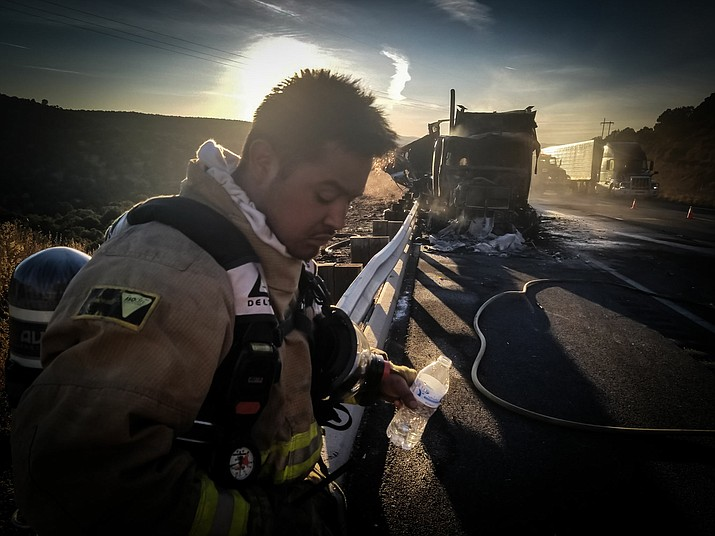 Ash Fork firefighter Cris Acosta takes a break after battling a semi-truck fire on I-40 Dec. 28.