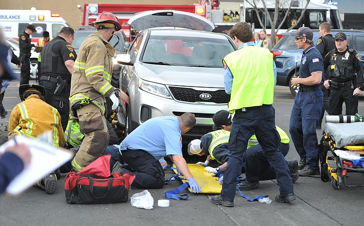 Emergency personnel from Central Arizona Fire & Medical, Prescott Valley Police and Lifeline Ambulance work to free a 101-year-old woman who was trapped under a van in the Glassford Hill Fry's parking lot late Wednesday morning, Jan. 3, 2018. (Les Stukenberg/Courier)