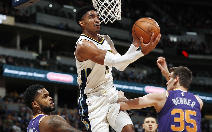 Denver Nuggets guard Gary Harris, center, goes up for a basket between Phoenix Suns guard Troy Daniels, left, and forward Dragan Bender, of Croatia, in the first half of an NBA basketball game Wednesday, Jan. 3, 2018, in Denver. (David Zalubowski/AP)