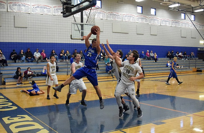 Camp Verde senior Ryan Loza pulls down an offensive rebound during the Cowboys' 72-70 win over No. 6 Eagar Round Valley on Saturday at Camp Verde Middle School. CV finished third at the Yvonne Johnson Memorial Tournament. (VVN/James Kelley)