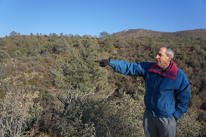 Local businessman Howard Mechanic points out the land along Overland Trail in the Government Canyon area where he hopes to develop a residential project. Because of the steep terrain, Mechanic says he plans to cluster the homes to preserve more of the parcel. In early December, Mechanic filed a complaint against the City of Prescott to acquire the water service to which he says the land is legally entitled. (Cindy Barks/Courier)