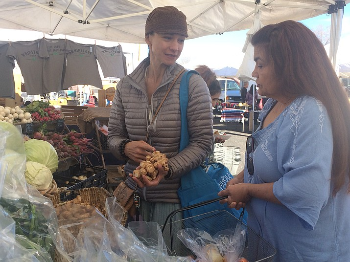 Diana Christensen and Maria Aubrey check out some sunchokes from Whipstone Farms at the Prescott Farmer's Market on Saturday, Dec. 30. (Jason Wheeler/Kudos)