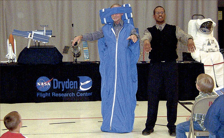 Mick Bowen, right, a representative of the National Aeronautics and Space Administration, gets help from Gene Myer in demonstrating how an astronaut dons a sleep restraint that attaches to a bulkhead aboard the International Space Station or in a space shuttle during a mission. The demonstration was given during a talk to parents and children Thursday night at Black Mountain School in Golden Valley. (Miner Photo/Terry Organ)