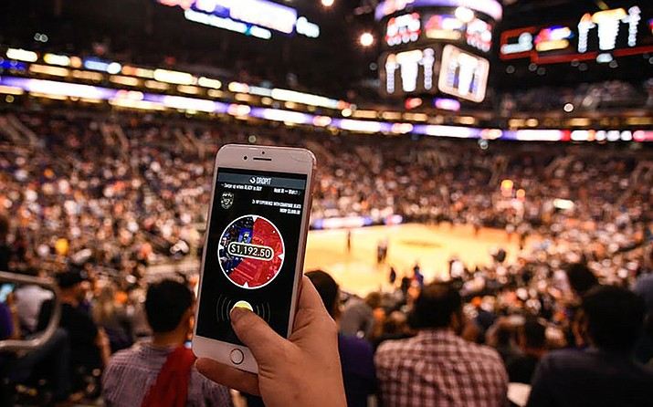 The app DROPIT has become part of the Suns in-game entertainment. Fans bid on auction items during a short period of time. (Photo by Kevin Palacios/Cronkite News)