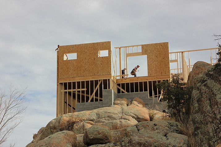 A construction crew works on building a home among the rocks in the Granite Dells area. (Max Efrein/Courier)