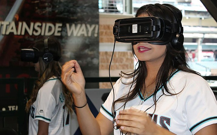 Virtual reality will likely be a bigger factor in the fan experience in the future. Here Arizona Diamondbacks employee Sienna Villa tries out a virtual reality headset in the Cox Connects VR Bullpen at Chase Field. (Photo by Samantha Pell/Cronkite News)