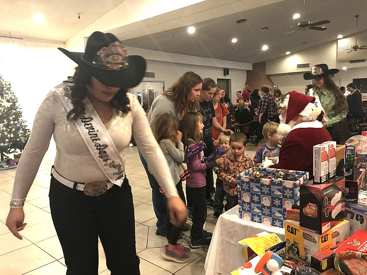 Andy Devine Days Rodeo Queens help Santa hand out gifts to about 100 kids within the span of two hours on Christmas Eve.
