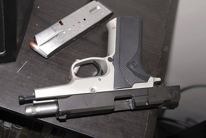 This 2014 photo provided by the Yakima Police Department shows a Smith & Wesson 9-mm pistol on a table in the apartment where Kyle Juhl used it to kill himself in Yakima, Wash. The pistol that Juhl used to kill himself was familiar to law enforcement: The Washington State Patrol had seized it years earlier while investigating a crime and then arranged its sale back to the public. It eventually fell into Juhl's hands, illegally. (Amber Ross/Yakima Police Department via AP)
