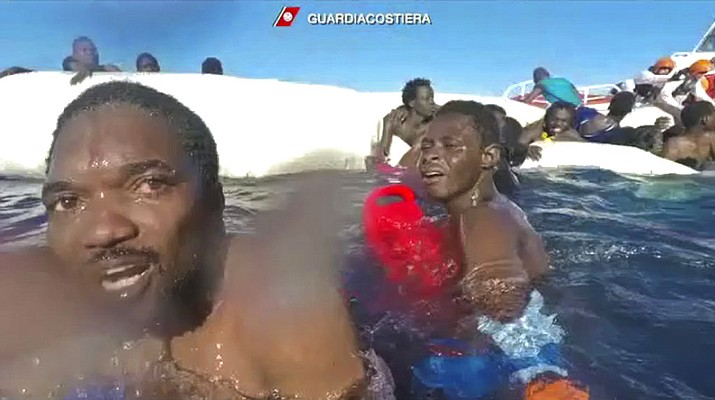 This frame of a video taken by the Italian Coast Guard on Jan. 6, 2018, in the Mediterranean Sea off Libya, shows migrants being rescued from dinghies as they try to cross to Italy. As many as 64 African migrants, including a mother whose surviving 3-year-old child desperately clung to her, are feared dead after a traffickers' overcrowded rubber dinghy from Libya started taking on water and deflating in the Mediterranean Sea. (Italian Coast Guard via Ap Photo)