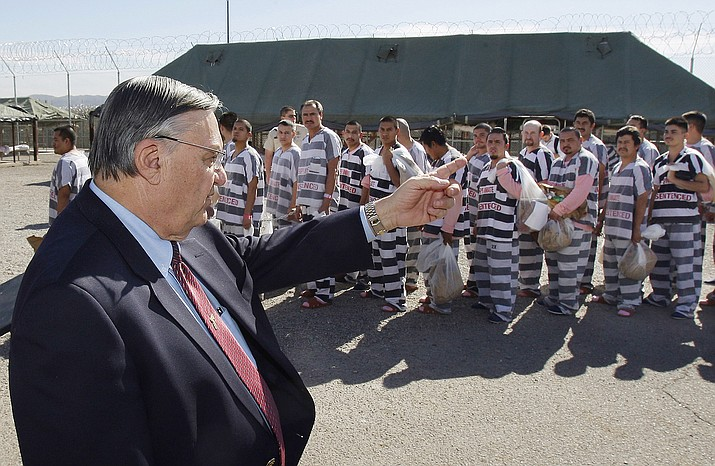 In this 2009, file photo, Maricopa County Sheriff Joe Arpaio orders approximately 200 convicted illegal immigrants handcuffed together and moved into a separate area of Tent City, for incarceration until their sentences are served and they are deported to their home countries, in Phoenix. (AP Photo/Ross D. Franklin, File)