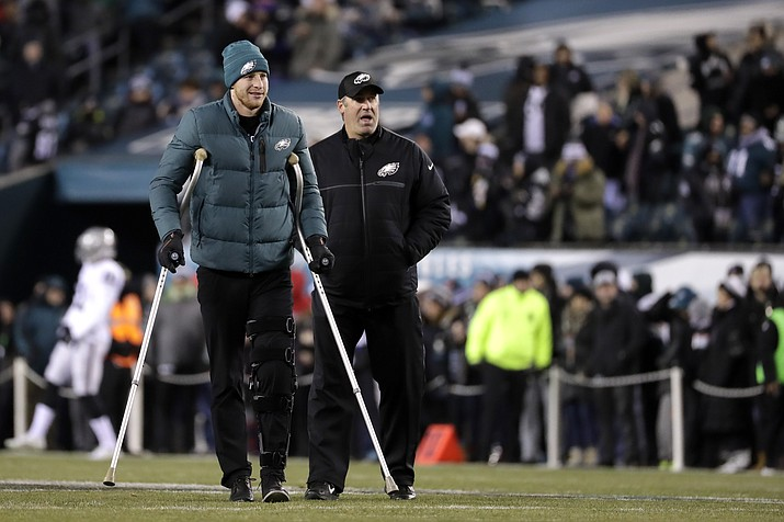 In this Dec. 25, 2017, file photo, Philadelphia Eagles' Carson Wentz, left, walks with head coach Doug Pederson, right, before an NFL football game against the Oakland Raiders in Philadelphia. (Michael Perez/AP, File)