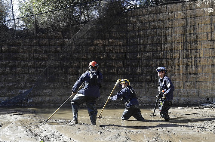 Members of the Los Angeles County Fire Department Search and Rescue crew work in mud and flooded waters in Montecito, Calif. Dozens of homes were swept away or heavily damaged and several people were killed Tuesday as downpours sent mud and boulders roaring down hills stripped of vegetation by a gigantic wildfire that raged in Southern California last month. (AP Photo/Marcio Jose Sanchez)