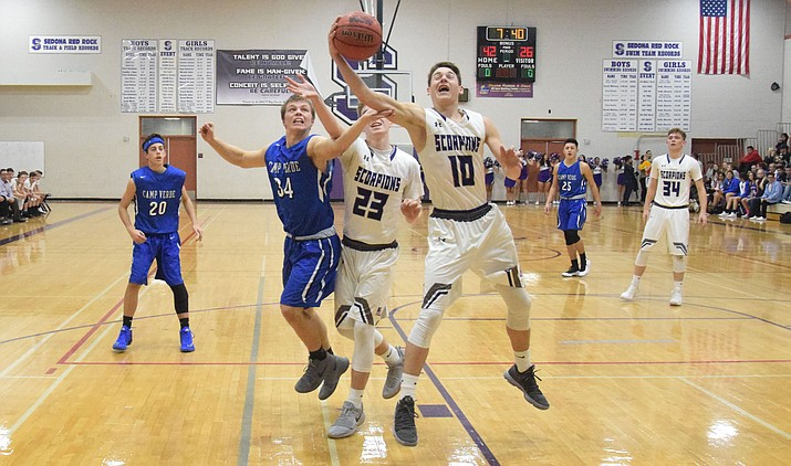 Camp Verde senior Ryan Loza goes for a rebound during the Cowboys' 69-51 loss at No. 17 Sedona Red Rock on Tuesday night. Loza had three rebounds against the Scorpions. (VVN/James Kelley)