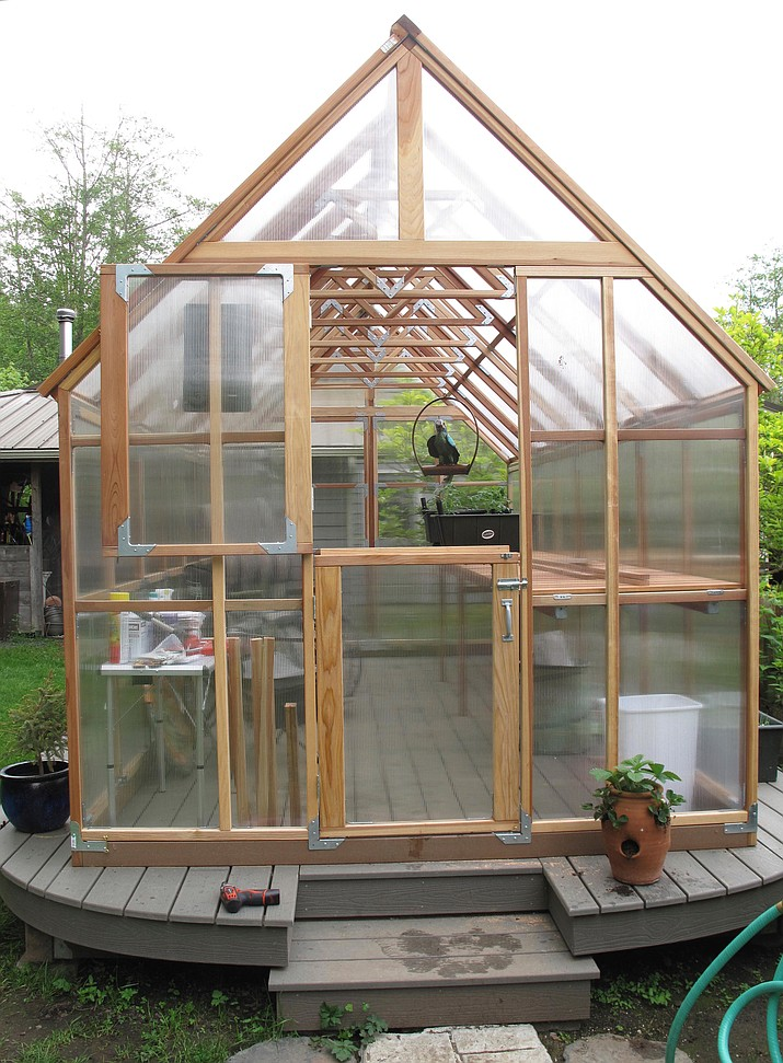 This May 11, 2013 photo shows a Hobby Greenhouse in a Langley, Wash., backyard. This greenhouse was built on a platform to prevent troublesome weed growth. Weed management in greenhouses, hoop houses and other enclosed settings include prevention, sanitation, use of landscape cloth, pulling by hand and very careful use of herbicides. (Dean Fosdick via AP)