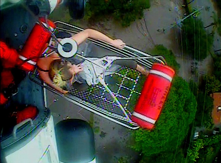 In this Jan. 9, 2018 image from video provided by the U.S. Coast Guard, a woman and an infant are hoisted aboard a Coast Guard helicopter as they are rescued from a flood-damaged home in Montecito, Calif. (U.S. Coast Guard via AP)