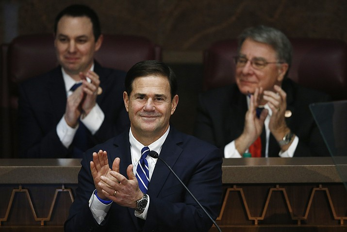 Arizona Republican Gov. Doug Ducey, middle, is joined by House Speaker J.D. Mesnard, left, R-Chandler, and Senate President Steve Yarbrough, right, R-Chandler, as they applaud Arizona women serving in government as Ducey gives his state of the state speech at the capitol, Monday, Jan. 8, 2018, in Phoenix. (Ross D. Franklin/AP)