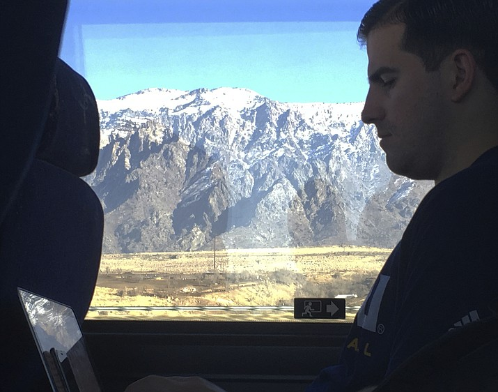 In this Jan. 5, 2018, photo, Northern Arizona assistant basketball coach Jason Sanchez goes over game film from the night before on a bus ride to Pocatello, Idaho. The Lumberjacks lost to Weber State by 40, then had to leave the next day on a two-hour bus ride for a game against Idaho State before driving back through Ogden to Salt Lake City. (John Marshall/AP)