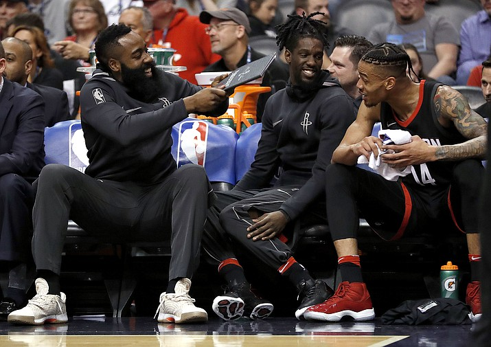 Houston Rockets guard James Harden, left, playfully fans his teammates on the bench during the first half Friday, Jan. 12, 2018, in Phoenix. (Matt York/AP)