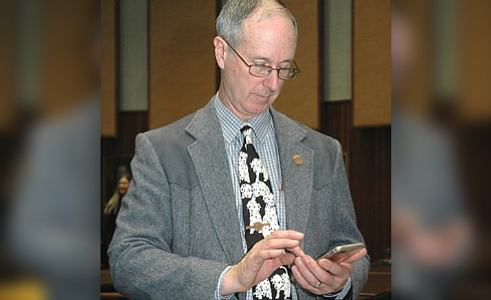 Rep. Bob Thorpe, R-Flagstaff looking at his cell phone. Thorpe has proposed a bill that would spell out that any records stored on the private cell phone, computer or social media of a public official or employee are not required to be disclosed. (Capitol Media Services 2017 file photo by Howard Fischer)