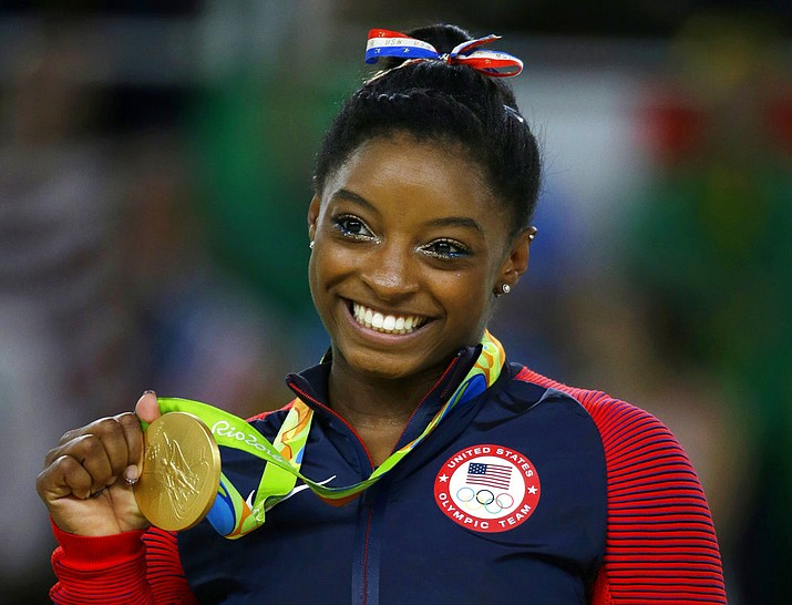 United States gymnast Simone Biles displays her gold medal for floor during the artistic gymnastics women's apparatus final at the 2016 Summer Olympics in Rio de Janeiro, Brazil. In a statement via Twitter on Monday, Jan. 15, 2017, Biles says she is among the athletes sexually abused by a now-imprisoned former USA Gymnastics team doctor.. (AP Photo/Rebecca Blackwell, File)
